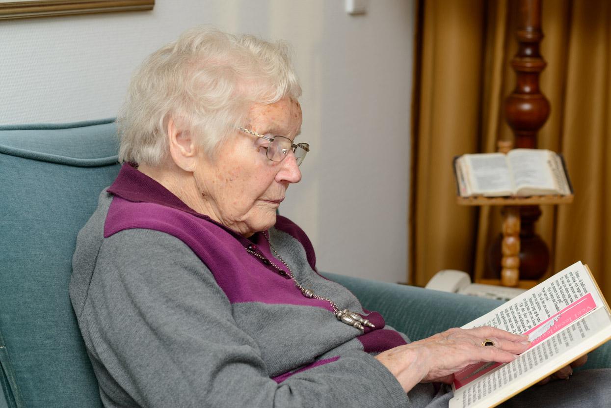 Oude dame leest in grote letter boek